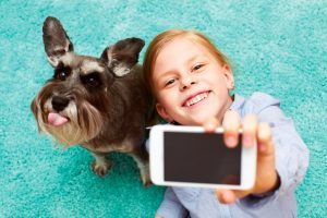 Girl photographing herself and her dog
